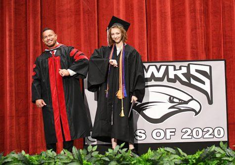 Nakiya Nyborg elbow bumps Principal McGill as she accepts her diploma and is filmed for this year