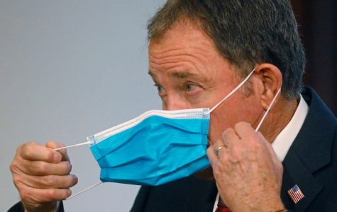 Governor Gary Herbert demonstrates the ease of wearing face masks in public to deter the spread of Covid-19.