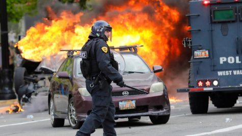 A policeman walks in front of a burning vehicle as protesters demonstrate Saturday, May 30, 2020, in Salt Lake City.