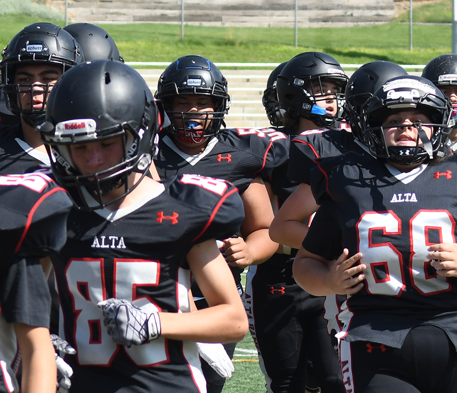 Saleen Reynolds, number 68, (far right) runs onto the field with her teammates on the Freshmen - Sophomore Alta football team.