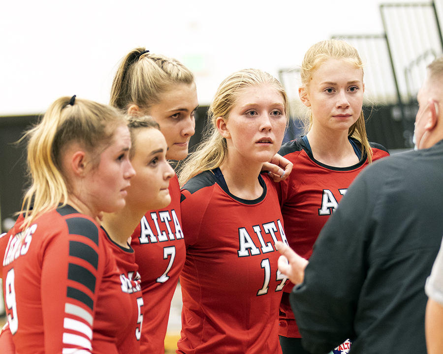 Members of the Varsity Team listen to Coach Zog during their game with Corner Canyon.