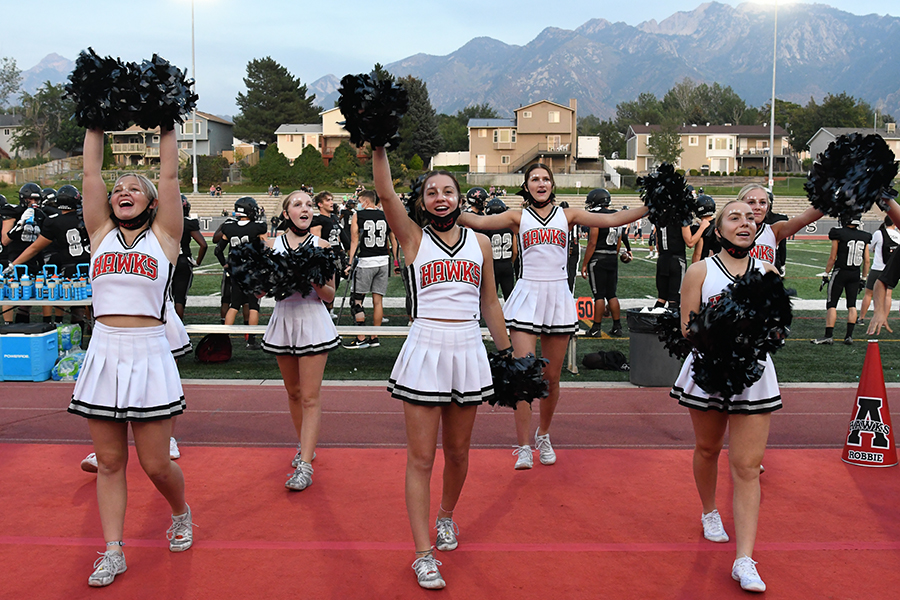 Alta cheerleaders, a fixutre at sports events, excite the crowd at this year's Homecoming game. Cheerleading is the most expensive