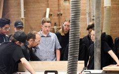 Mr. Joey Newman works with woodworking students.