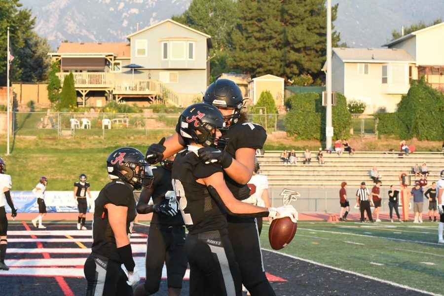 Team members celebrate a touchdown in the end zone against Maple Mountain.